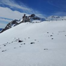 Though snowpack is supports a snowmobile, there are exposed rocks above treeline.
